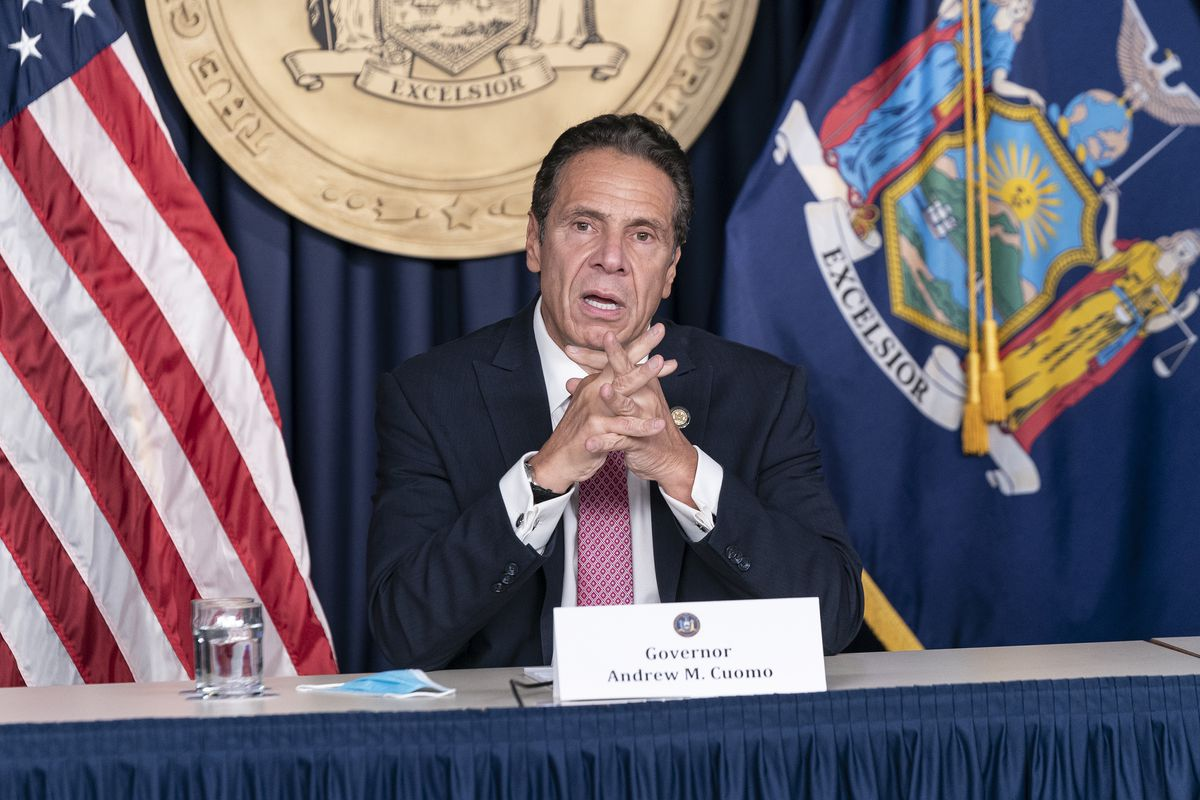 Cuomo sits in at a gray table in front of the seal of New York, as well as the state and US flags. In a dark suit, white shirt, and pale red tie, he speaks with his hands clasped.