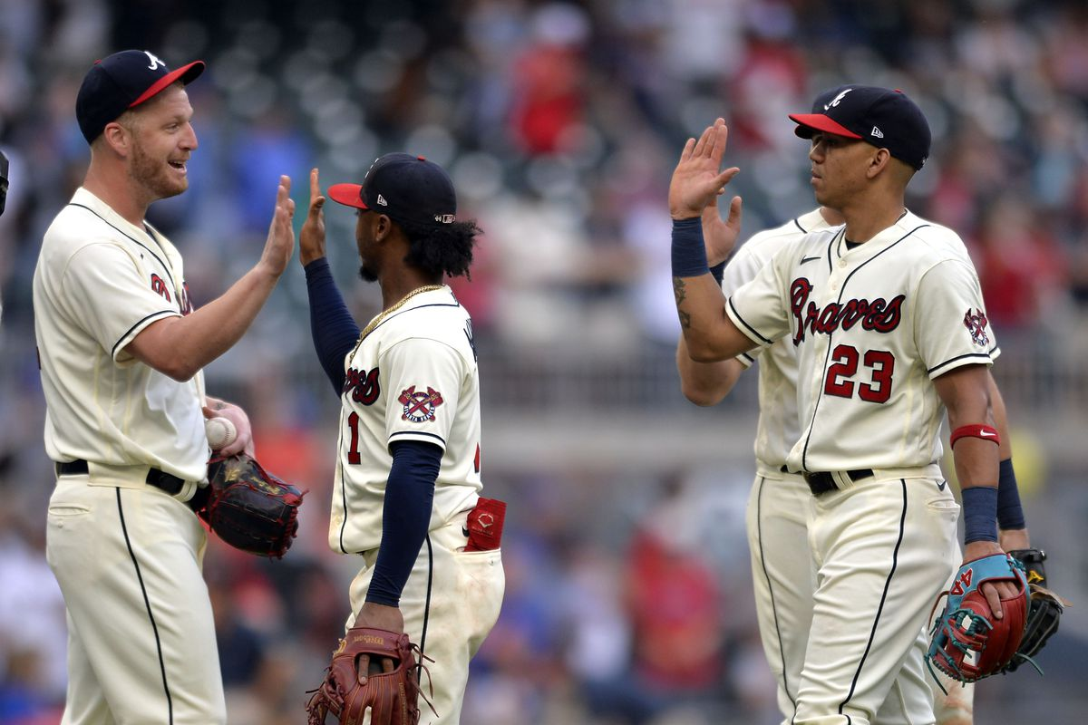 Will Smith #51, Ozzie Albies #1, and Ehire Adrianza #23 of the Atlanta Braves celebrate after winning against the New York Mets at Truist Park on October 3, 2021 in Atlanta, Georgia.