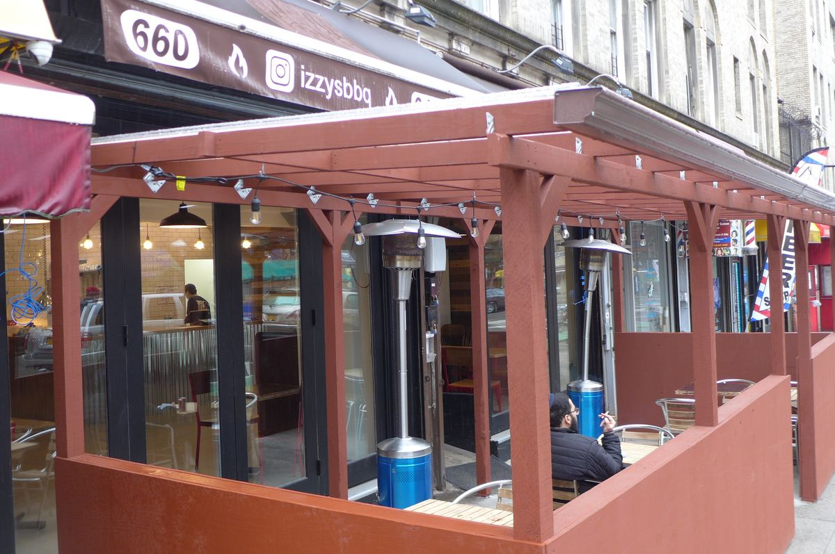 An outdoor seating are in front of an awning with the name of the restaurant on it.