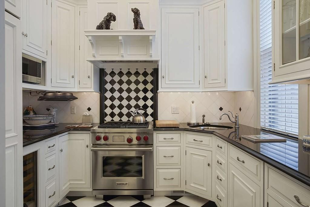 A small kitchen with a U-shaped counter and a striking tile pattern.