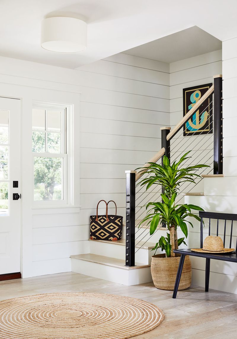 A home entryway decorated with shiplap walls, and a modern staircase banister made with tautly strung wire in between black painted pillars. There is a a tall palm-like houseplant potted in a natural colored basket sitting next to an antique looking black bench.