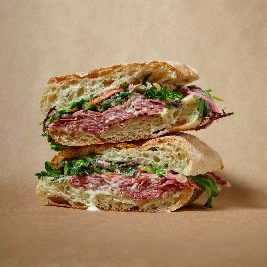 Two halves of a pastrami sandwich sit on top of each other at a Pasture pop-up.