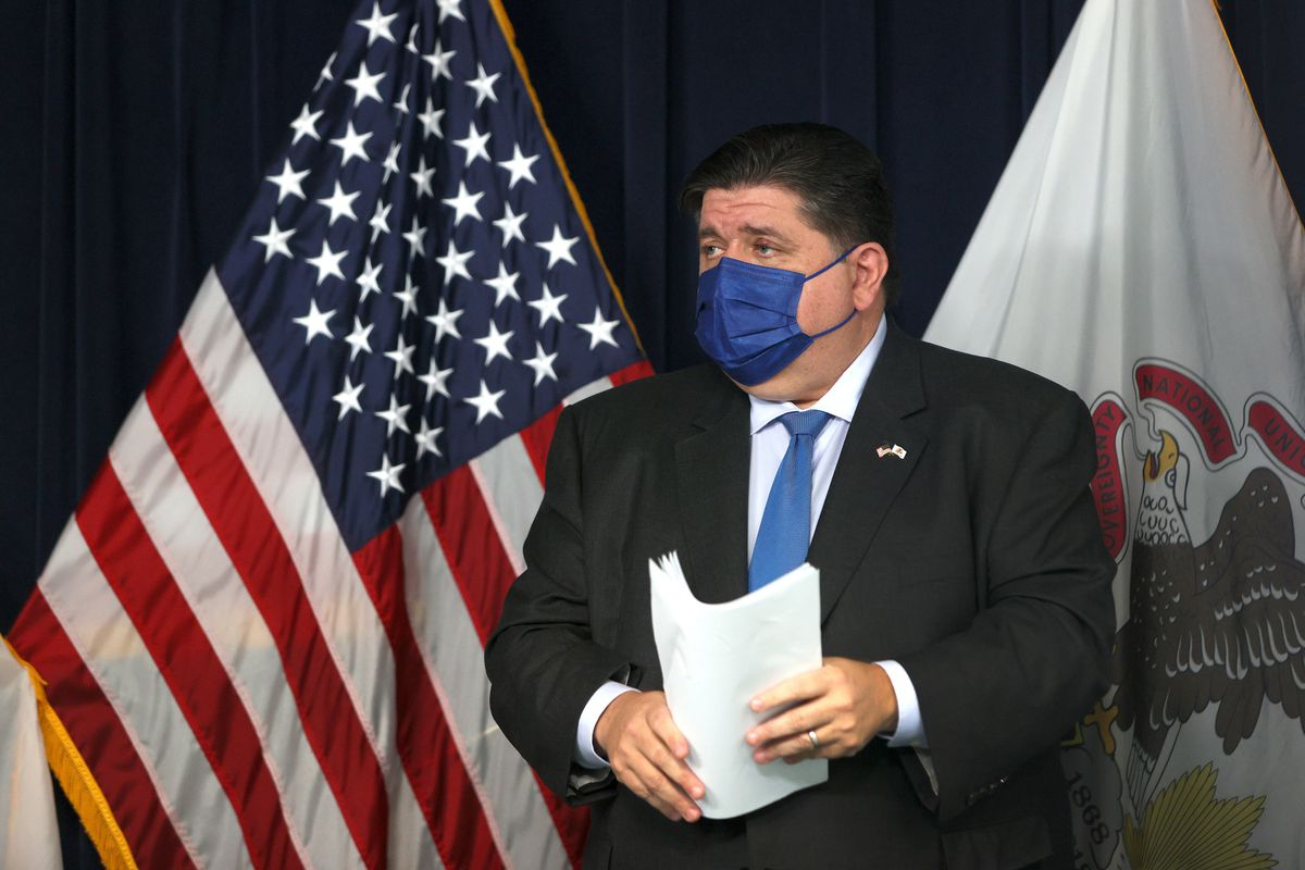 Governor J.B. Pritzker holds papers and stands on a stage in front of the United States flag, wearing a blue mask.