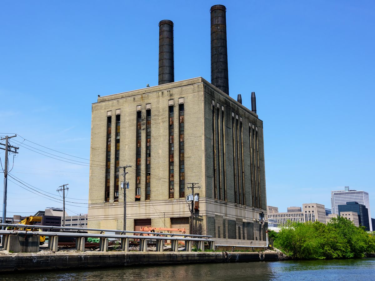 A windowless brick building with two large smoke stacks on top.