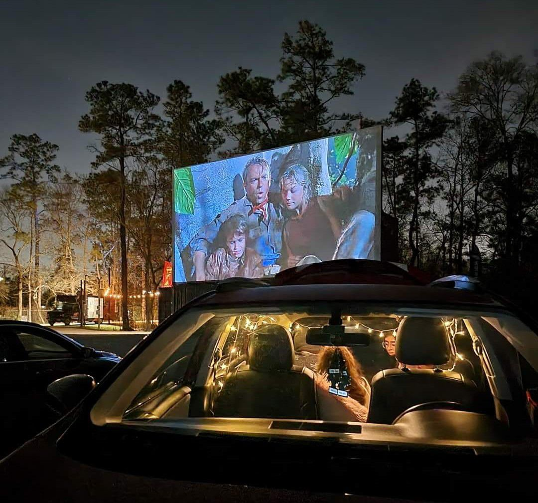 people in a lit car watching a film on a large screen at a drive-in theater