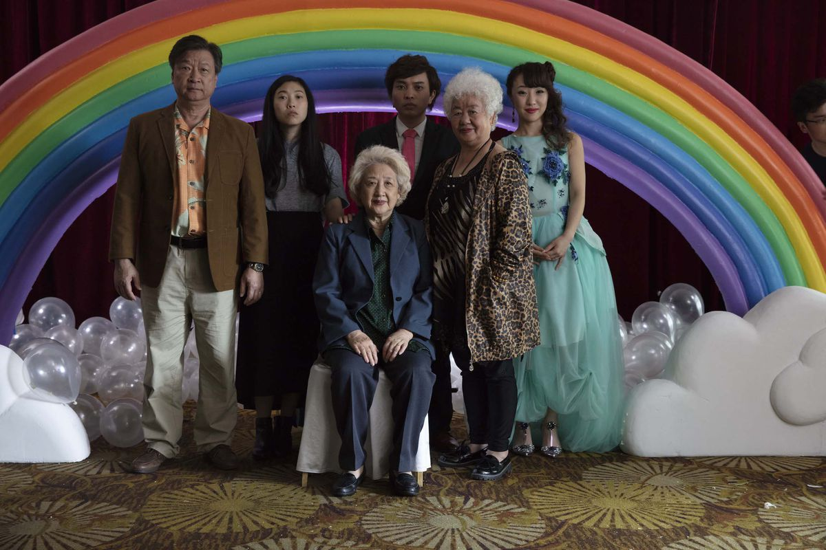a Chinese family stands in front of a rainbow structure in The Farewell