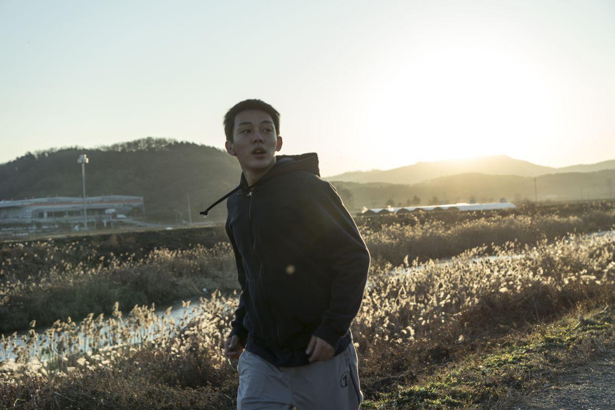 Jong-su (Yoo Ah-in) wanders through a field.