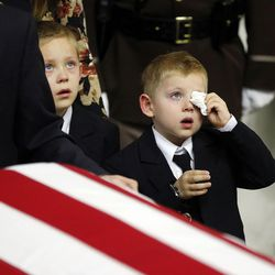 Bennett Ellsworth, left, and his brother, Ian, right, accompany the casket of their father, Utah Highway Patrol trooper Eric Ellsworth, into the Dee Events Center in Ogden on Wednesday, Nov. 30, 2016. Ellsworth, 31, of Brigham City, was hit by a car on Nov. 18 while trying to direct other vehicles around a traffic hazard along a rural stretch of state Route 13 at 13600 North near Garland, Box Elder County. He died Nov. 22 after several days in the intensive care unit at Intermountain Medical Center.