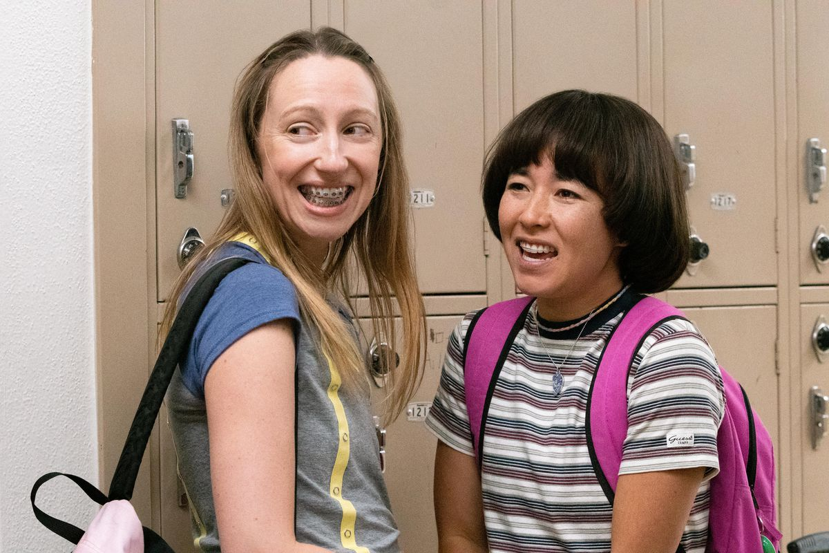 Anna Konkel and Maya Erskine wear backpacks and smile next to a row of tan lockers in Pen15.