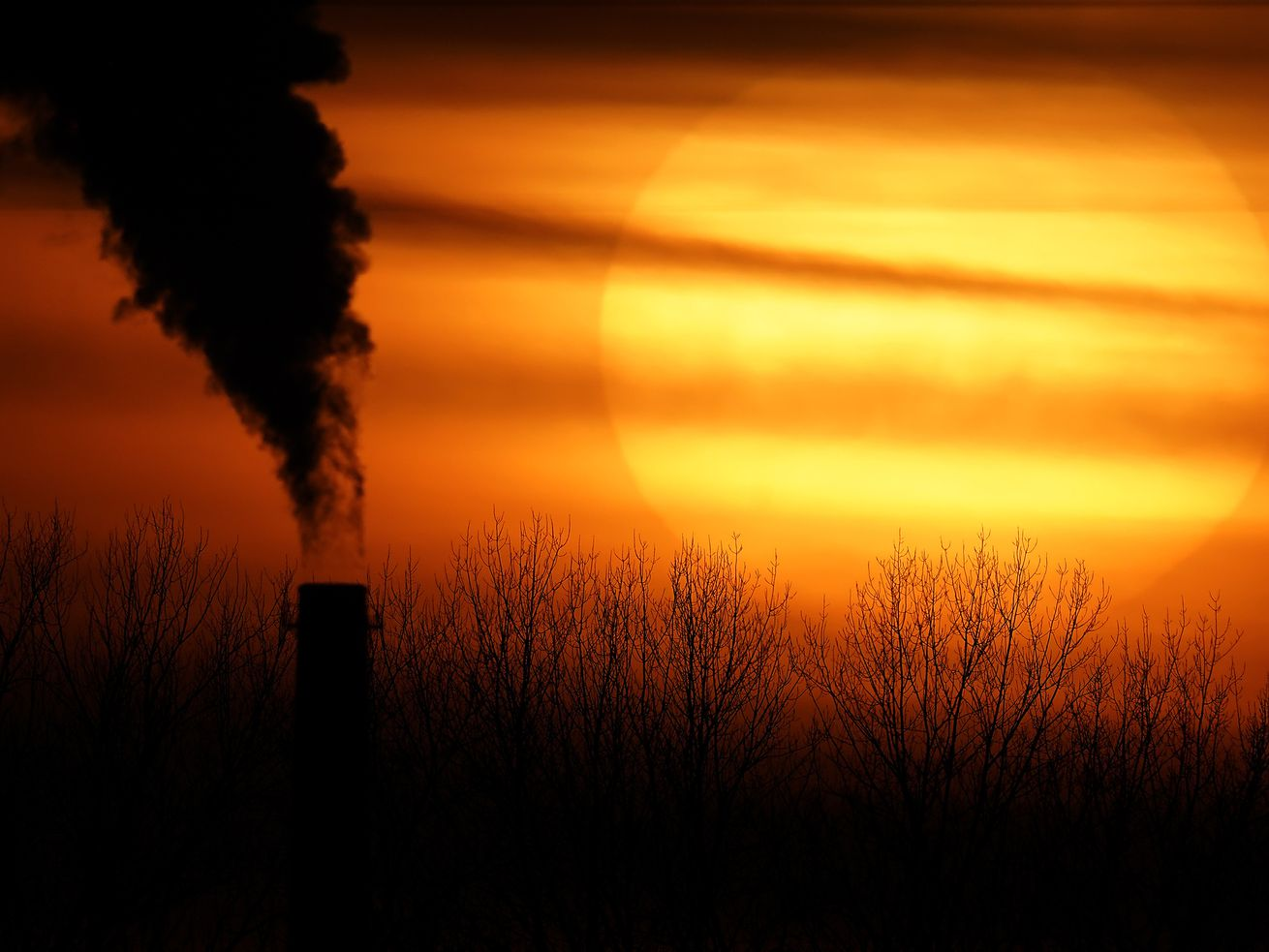 In this Feb. 1, 2021 file photo, emissions from a coal-fired power plant are silhouetted against the setting sun in Independence, Mo.