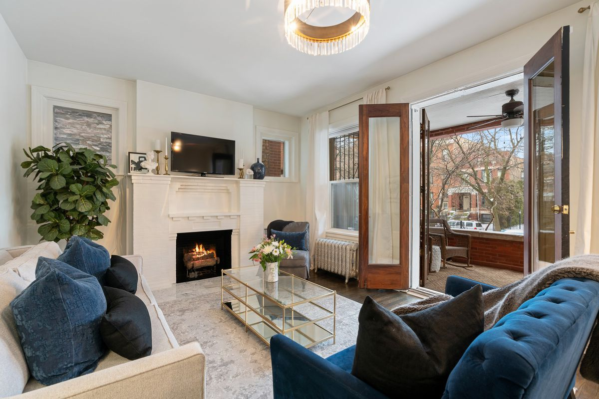 A bright living room with double doors opening to a terrace. The room has a white brick fireplace and two sofas.