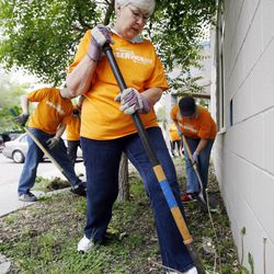Gail Miller works in the flower bed as employees of the Larry H. Miller (LHM) Group of Companies pay tribute to the late Larry H. Miller by participating in community service projects in Salt Lake City, Thursday, April 26, 2012, Employees in seven western states participated.