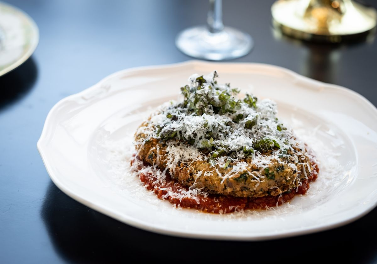 A breaded cut of pork sits atop marinara sauce, sprinkled with parmesan cheese, at Orfano in Boston's Fenway neighborhood
