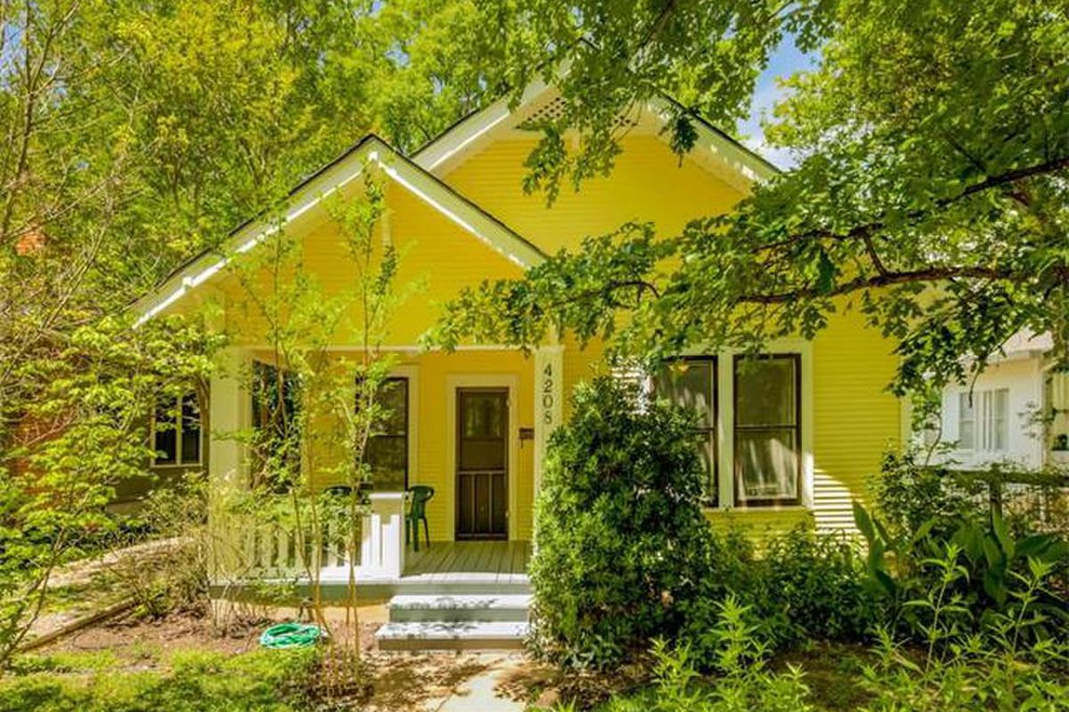 Bright yellow wooden 1928 bungalow