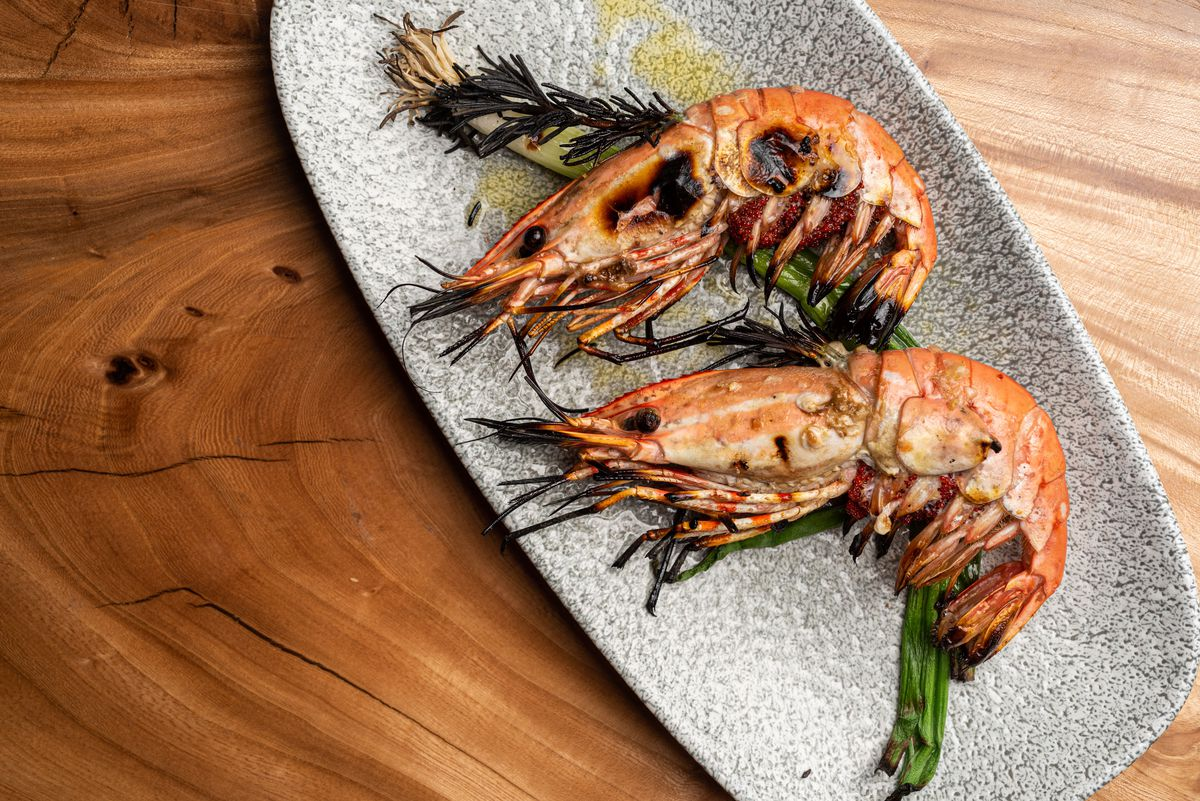 Grilled shrimp on a long plate with wooden table in back.