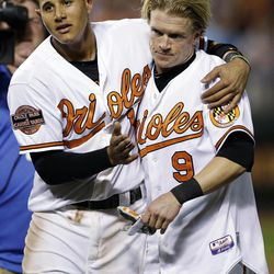 Baltimore Orioles' Manny Machado, left, celebrates with Nate McLouth after scoring the game-winning run on McLouth's single in the ninth inning of a baseball game against the Tampa Bay Rays in Baltimore, Wednesday, Sept. 12, 2012. Baltimore won 3-2.