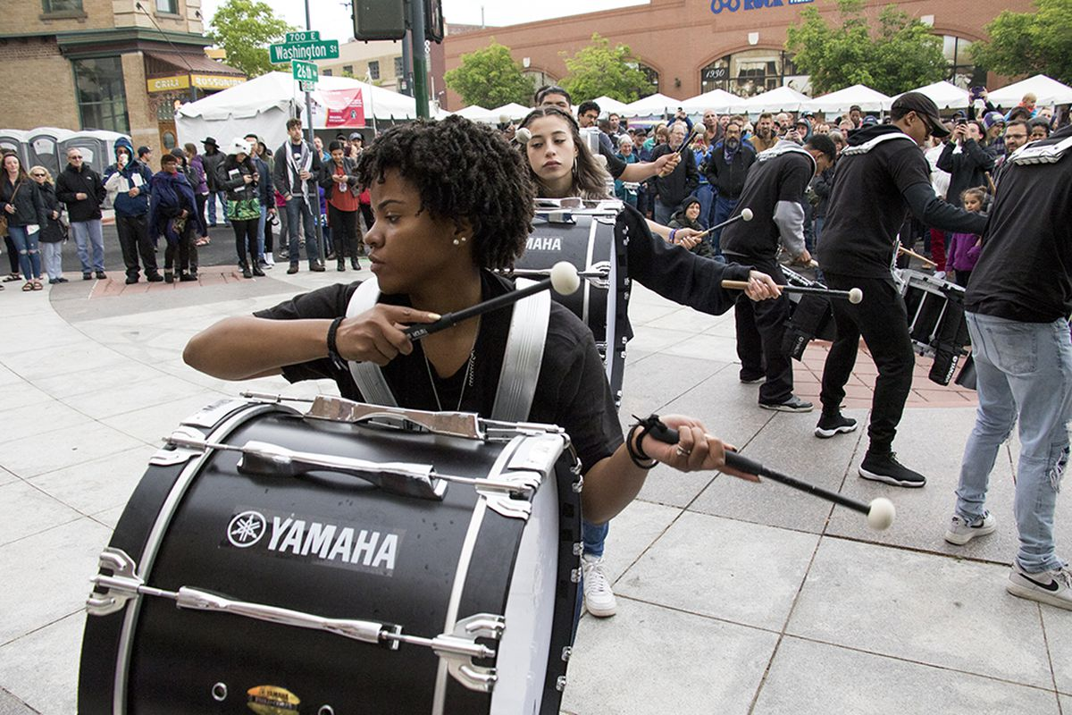 A student performs in a drumline in a courtyard.
