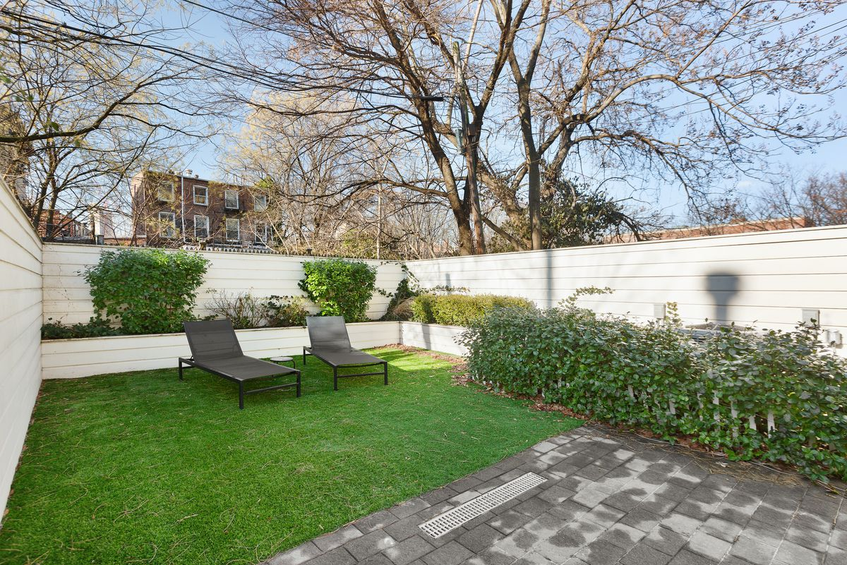 A backyard with shrubs and a white fence.