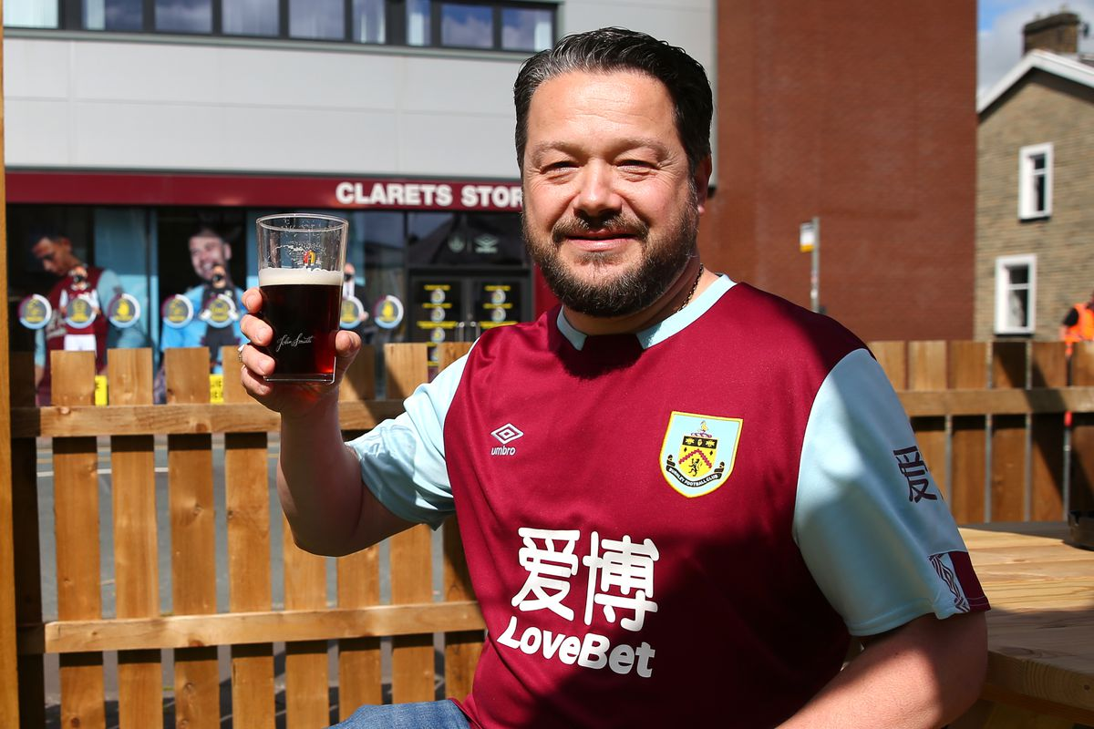 Burnley fan enjoys a beer at the pub outside the stadium prior to a match - Premier League