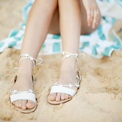 """Erin Hagstrom of <a href=""""http://calivintage.com"""">Calivintage</a> lounges in the sand in her Loeffler Randall star-strap sandals."""