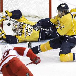 Nashville Predators goalie Pekka Rinne, of Finland, and Mike Fisher (12) reach for a shot-attempt by Detroit Red Wings center Henrik Zetterberg (40), of Sweden, that sailed high in the third period of Game 1 of a first-round NHL hockey playoff series on Wednesday, April 11, 2012, in Nashville, Tenn. The Predators won 3-2.