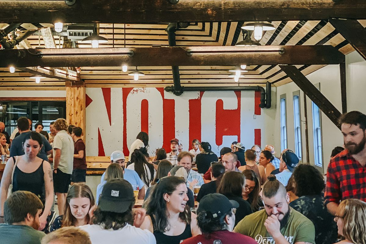 """A crowd is gathered in a beer garden in Brighton, MA. The crowd is backdropped with a large red sign with the word """"Notch"""" printed on it in white. The walls are white, and there are vaulted wood slat ceilings."""