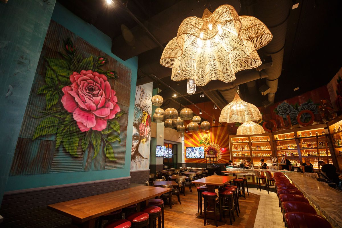 A colorful restaurant interior featuring a large mural of a rose and other Mexican-inspired art