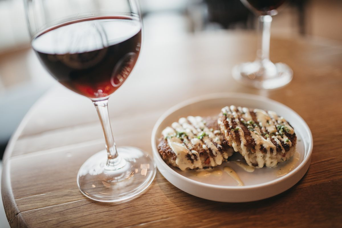 A glass of red wine next to a plate of two crab cakes drizzled with sauce.