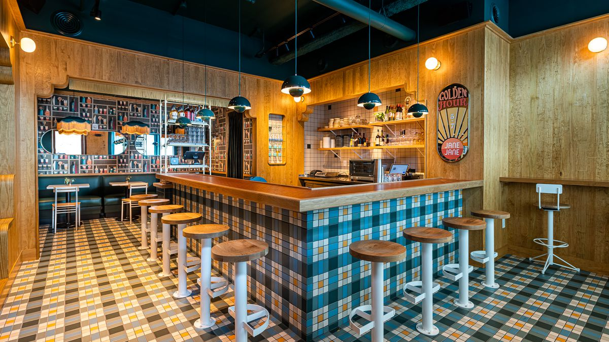 A mosaic of green-and-white plaid tiles runs across the floor and up the front of a wood-paneled bar surrounded by built-in stools at Jane Jane