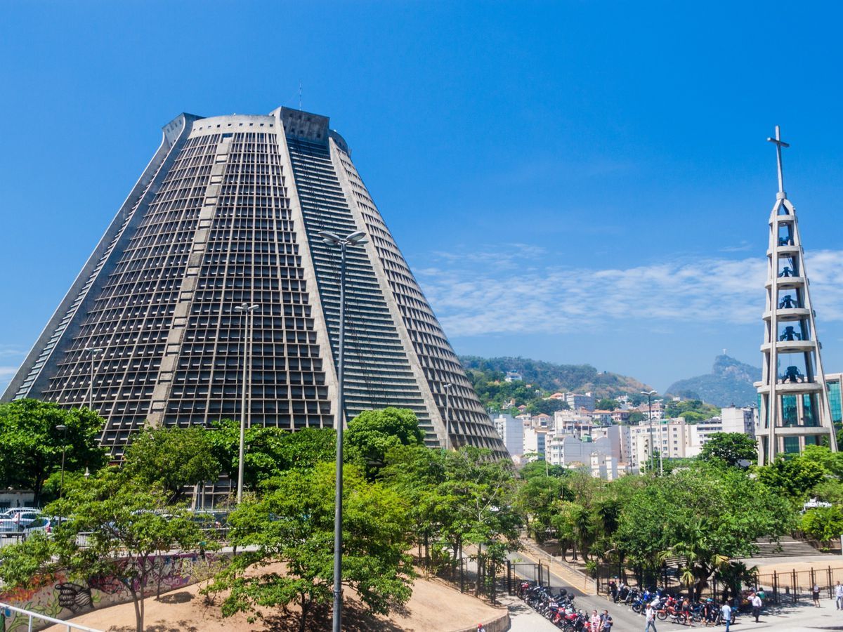 The exterior of the Catedral Metropolitana de Sao Sebastiao. The building has a pyramidal structure. There are trees in front.