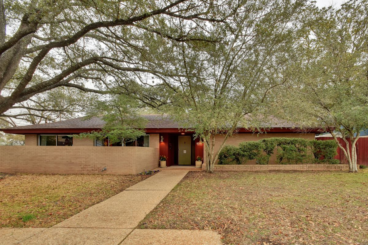 Low-slung, large ranch house with off-white brick, walled front courtyard, red trim, big oaks