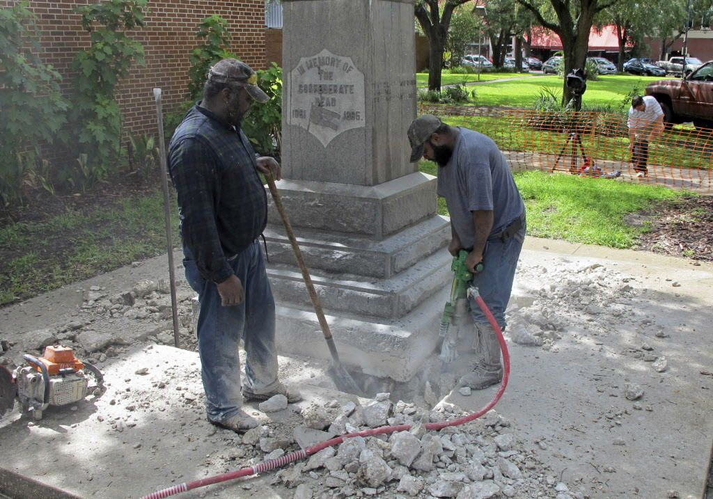Workers begin removing a Confederate statue in Gainesivlle, Florida, on Monday, Aug. 14, 2017. The statue is being returned to the local chapter of the United Daughters of the Confederacy, which erected the bronze statue in 1904.   Jason Dearen/AP