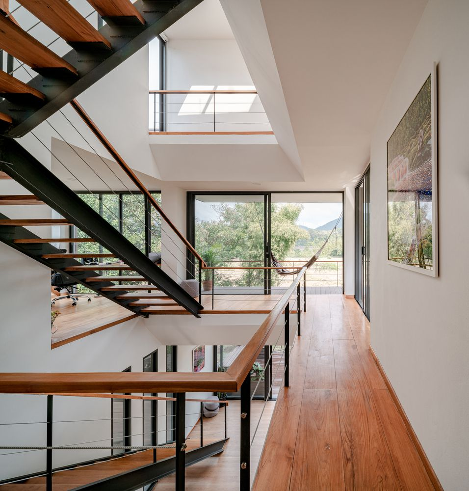 Airy house with central staircase and glass walls to a balcony.