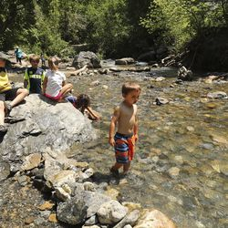 Sawyer Brooks and his friends play in the American Fork River near Timpanogos Cave in American Fork Canyon on Tuesday, July 21, 2020. Visits to all national parks in Utah this summer are drastically down with the exception of Timpanogos Cave.