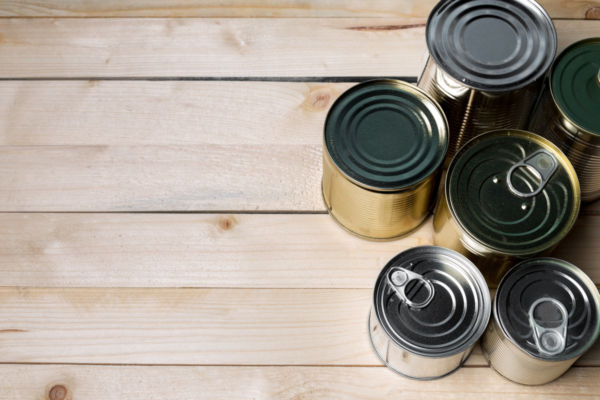 A small collection of canned food on a wooden table