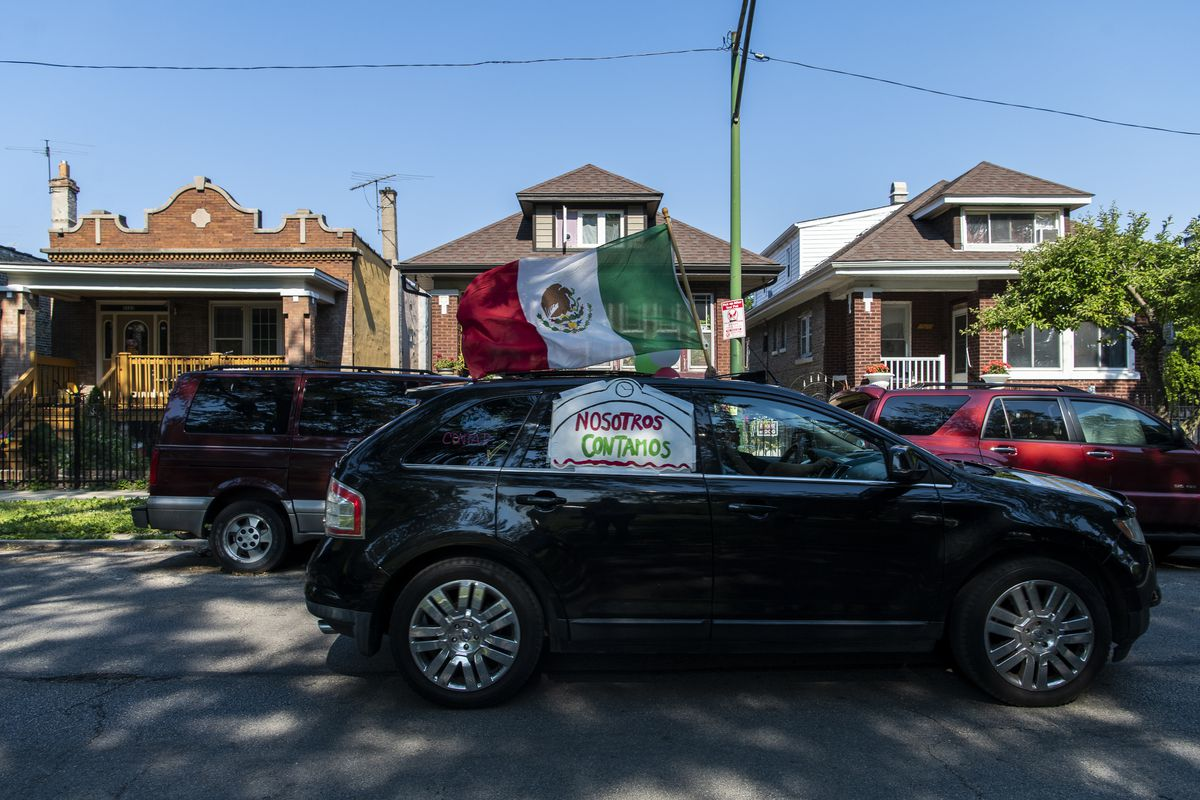 A vehicle zooms through the Little Village neighborhood with its horn blaring and its lights flashing to remind people to fill out their 2020 census.