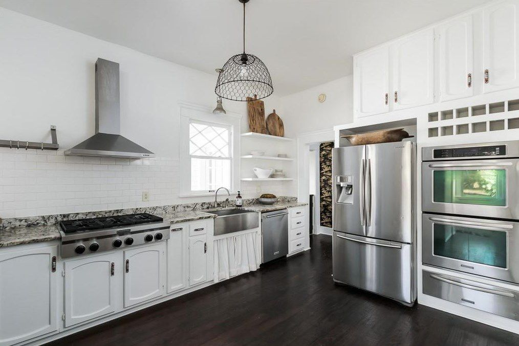 A big white kitchen with stainless steel.