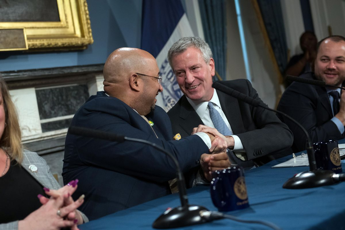 Mayor Bill de Blasio shakes hands with District Council 37 Executive Director Henry Garrido after announcing a contract agreement in 2019.