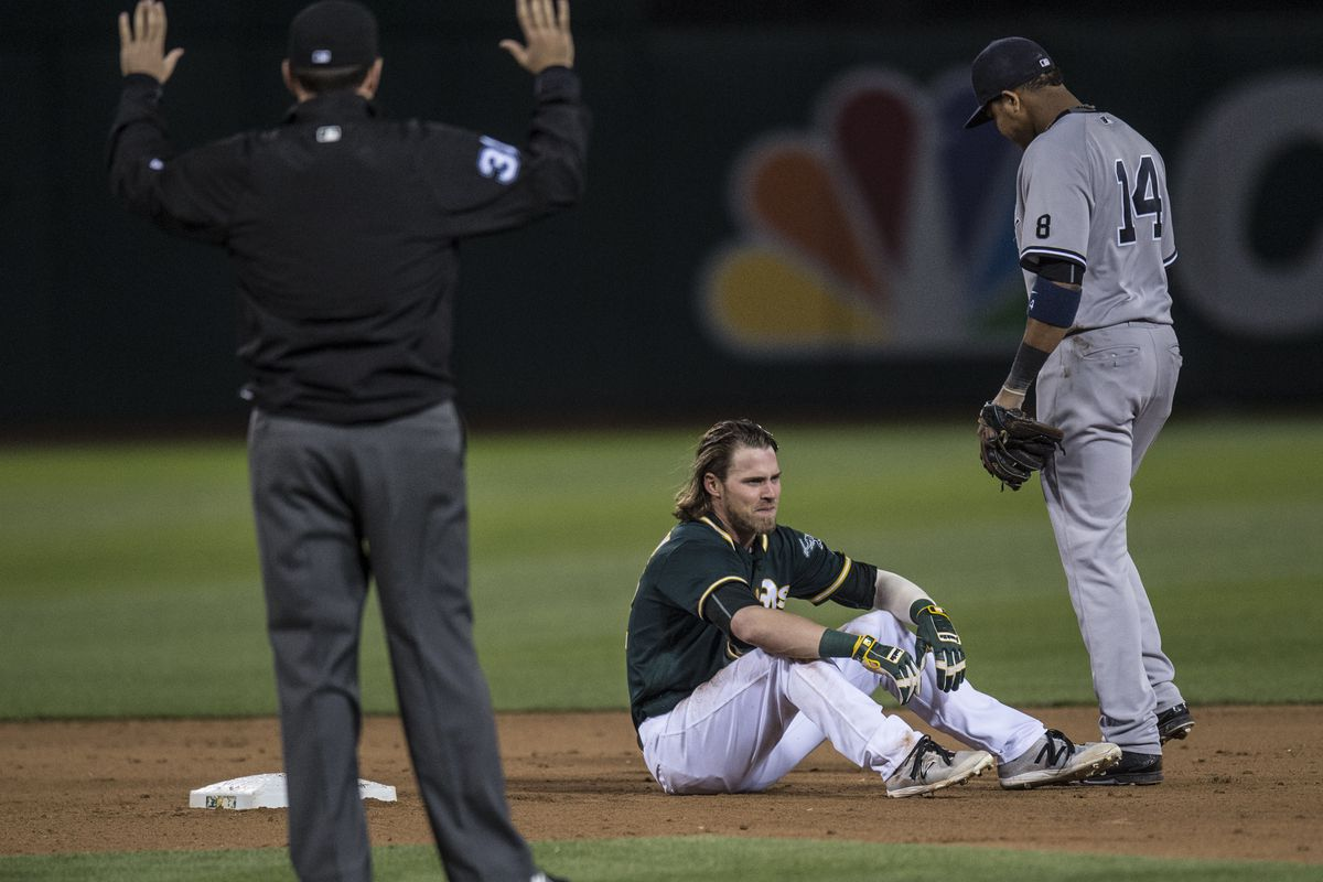 Josh Reddick sits after his hand was injured stealing second base.