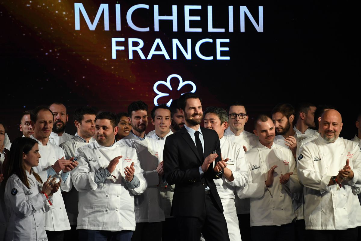People on stage in front of a Michelin sign
