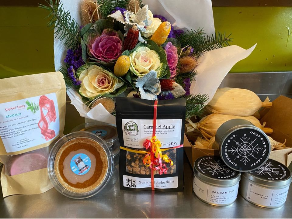 A collection of gifts, including tea, pies, and a bouquet of flowers