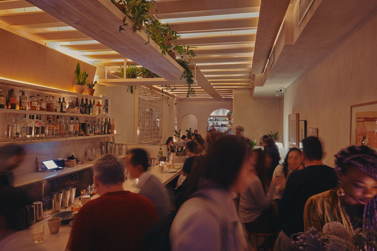 Patrons pack the front bar room at Llama San while vines creep down from the ceiling