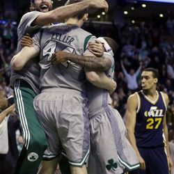 Boston Celtics center Tyler Zeller (44) is mobbed by teammates Luigi Datome, left, and Isaiah Thomas, right, after he hit the game-winning shot in an NBA basketball game against the Utah Jazz in Boston, Wednesday, March 4, 2015. The Celtics won 85-84. Utah Jazz center Rudy Gobert (27) reacts at right. (AP Photo/Elise Amendola)