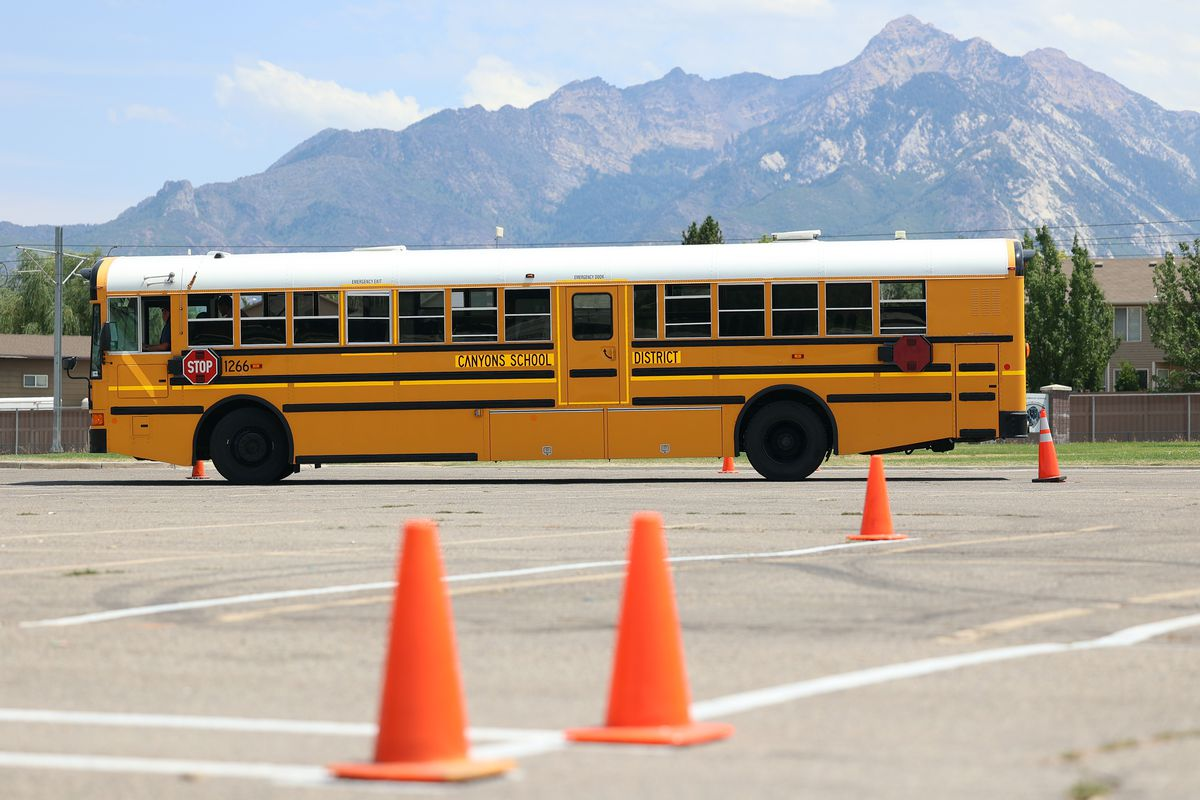A student driver and instructor navigate a bus around cones in a parking lot at a Canyon School District building in Sandy on Monday, July 19, 2021. From bus drivers to school nutrition workers, districts are facing challenges filling critical support positions amid a post-pandemic labor shortage. Canyons School District is offering $21 to lure qualified employees.