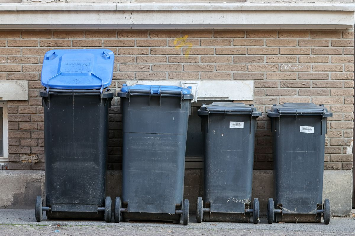 Waste bins for cardboard and paper as well as for residual waste are located on a house wall.