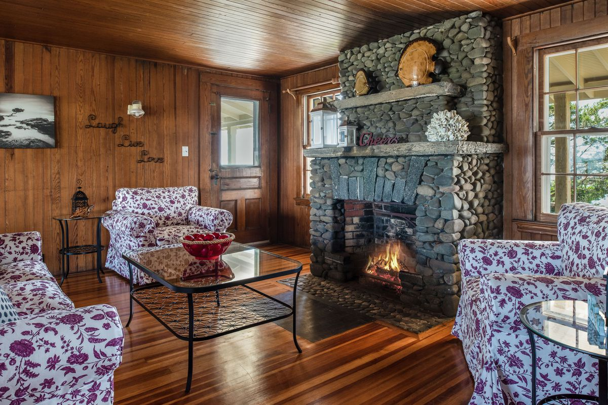 A living room has wood floors, floral couches, and a large stone fireplace.