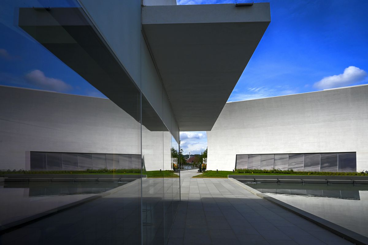 Two modern pavilions made of gray material. One has an overhang. The sky above them is deep blue.