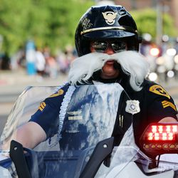 A Salt Lake motorcycle officer sports a large fake mustache as the Days of '47 Parade in Salt Lake City kicks off on Friday, July 23, 2021.