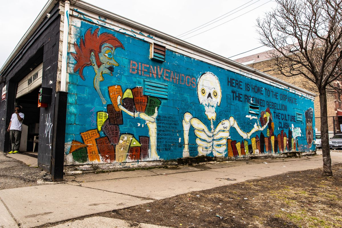 """Sam Kirk's first mural """"The Culture Clash"""" at 1708 S. Ashland Ave. speaks to displacement in Pilsen resulting from gentrification."""