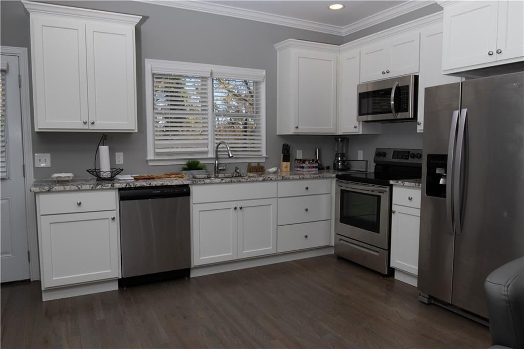White kitchen with stainless appliances and dark hardwood floors.